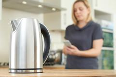 Woman Controlling Smart Kettle Using App On Mobile Phone Stock Photos