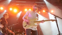 Man playing on an electronic guitar and singing on a rock concert Stock Footage