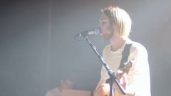 The man playing on a guitar and sing a song in microphone on a concert Stock Footage
