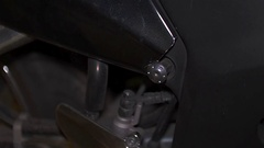 Mechanic wearing gloves screws away and removes metal bolt from two black Stock Footage
