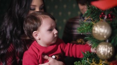 A family at a New Year tree. The kid on hands at mother is played by a Christmas Stock Footage