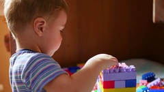 A young child plays in the constructor. Game of the children's designer. Colored Stock Footage