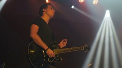 Charismatic guitarist playing on a electronic guitar on a rock concert Stock Footage