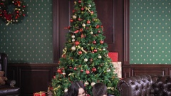 A young and happy family sitting near a festively decorated Christmas tree and Stock Footage