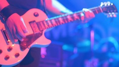 Close-up - man playing on an electronic guitar with mediator on a concert Stock Footage