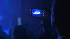 The fan shooting the video on a phone during the rock concert Stock Footage