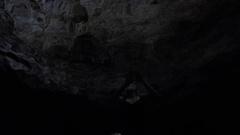Underwater shot of pretty woman swimming in dark cenote Stock Footage