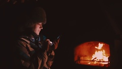 Winter. The girl in a jacket and hat outdoors near the fireplace. In the hands Stock Footage