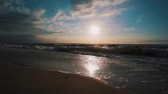 Surge of water run on sand shore coastline, summer evening setting sun Stock Footage