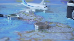 Travel accessories and toy plane on world map background, vacation planning Stock Footage