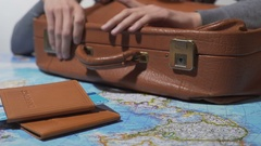 Man ready for trip with packed suitcase and tickets, dreaming about vacation Stock Footage
