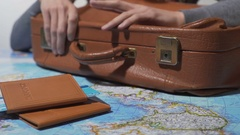 Tourist ready for vacation tapping fingers on old suitcase, travel around world Stock Footage