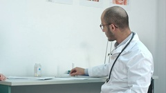 Male doctor shaking down thermometer and handing it to the patient Stock Footage