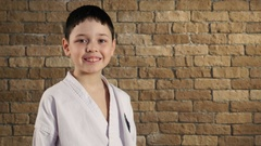 A seven year old kid, dressed in kimono, smiles slightly in studio with a brick Stock Footage