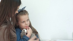 Doctor trying to cheer up little girl patient hugging her bunny toy Stock Footage