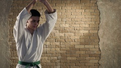 A young karateka delivers chopping katana strikes  in studio Stock Footage