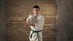 A young karateka delivering oblique chopping strike with his katana in studio Stock Footage