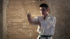 Katana usage at a workout of a young karateka in a white kimono in studio Stock Footage