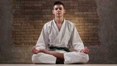 A teen boy in a white karate kimono sits in Lotus pose and meditates Stock Footage