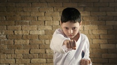 A small kid trains hitting with his hands, dressed in a white karate kimono Stock Footage