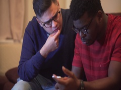 Two young men argue over mobile phone use. Black and Asian young males Stock Footage