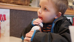 A boy drinking his chocolate milk in a fast food place Stock Footage