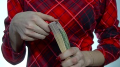 Young woman in red dress counts a pack of money in hands in slow motion Stock Footage