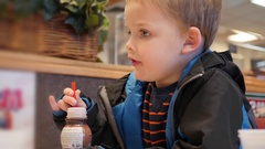 Boy drinking his chocolate milk in a fast food place Stock Footage