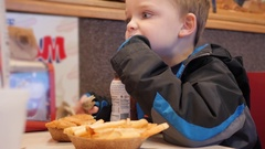 Boy drinks chocolate milk in a fast food place Stock Footage