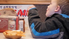 Boy eating chicken fingers and french fries in fast food place Stock Footage
