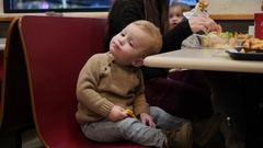 Little toddler with family eating grilled cheese at fast food restaurant Stock Footage