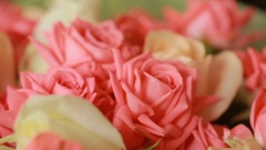 A delightful bouquet of peach and pale pink roses in a green-mesh packing Stock Footage
