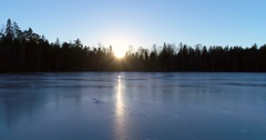 Cinema 4k aerial flight above the ice, on a blue pond, at a evening sunset,.. Stock Footage