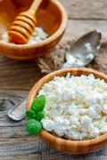 Homemade cottage cheese in a round wooden bowl. Stock Photos