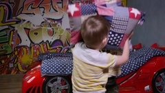 Little kids twin brothers fighting with pillows at home having fun Stock Footage