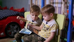 Little twin kids brothers at home watch tablet cartoons sitting on chairs Stock Footage