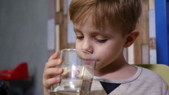 Little cute kid boy drink clear pure water from a glass cup - healthy childhood Stock Footage