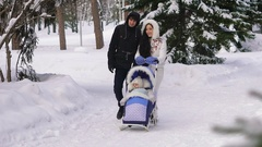 Young beautiful dressed parents walking on snow-covered park with your child Stock Footage