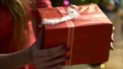 Girl twirls its in the hands of the closed new year's gift Stock Footage