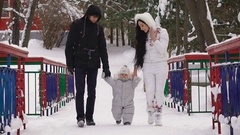 Father and mother with her son walk down an alley in a winter park holding baby Stock Footage