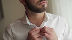 Man dressing close-up shallow dof. Male hands buttoning white shirt quickly Stock Footage