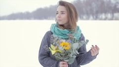 Love with a girl in a gray sweater with a bouquet of flowers on a frozen lake . Stock Footage