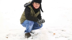 Happy child boy playing with a snow on a snowy winter park  Stock Footage