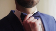 Male hands adjusting blue bowtie closeup. Well-dressed man touch puts bow tie Stock Footage
