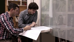 Two design engineer checking construction drawings Stock Footage