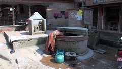 Woman takes water from a well on streets of Kathmandu in Nepal. Stock Footage