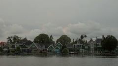 Timelapse of clouds over houses on river bank, Netherlands Stock Footage