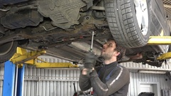 Male auto mechanic with spanner working under car in garage Stock Footage