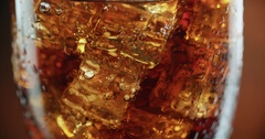 Cola with ice. Extreme close-up, drink through a straw for a coke with ice cubes Stock Footage
