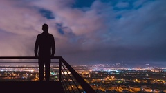 The man stand on the balcony on the background of the night town. Time lapse Stock Footage